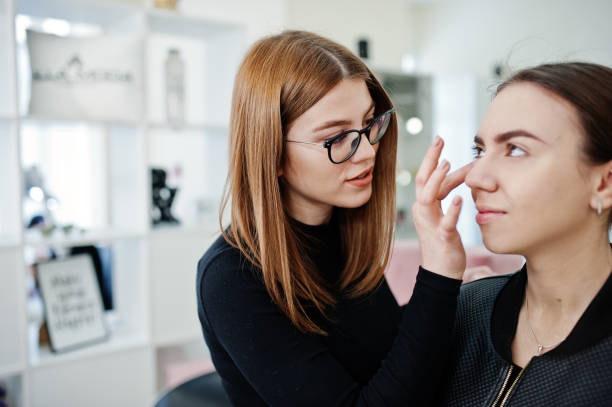Make up artist work in her beauty visage studio salon. Woman applying by professional make up master. Beauty club concept. stock photo