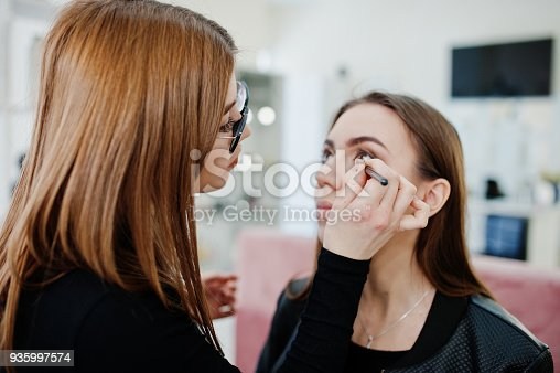 istock Make up artist work in her beauty visage studio salon. Woman applying by professional make up master. Beauty club concept. 935997574