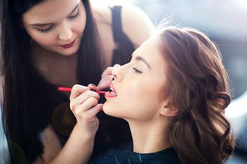 Make up artist working on client