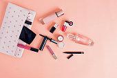メイクアップバッグと化粧品に隔てられたピンクの背景