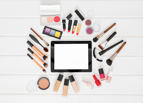 Make up , brushes and tablet computer on white background