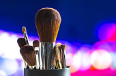Make up brushes set on abstract blue pink purple bokeh background. Colorful advertisement for marketing cosmetics and beauty services or tutorials. Bright blurred city lights.