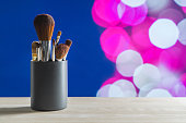 Make up brushes set on table in container. Cover image or ad for tutorials or business services in beauty industry. Abstract dark blue and pink bokeh balls background.