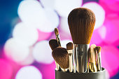 Make up concept on pink and purple background. Close up of beauty brushes set on abstract backdrop. Modern and stylish look. Bokeh balls and city lights.