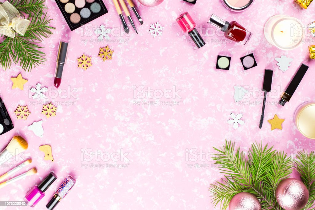 Make up cosmetics and Christmas decorations on artistic pink...