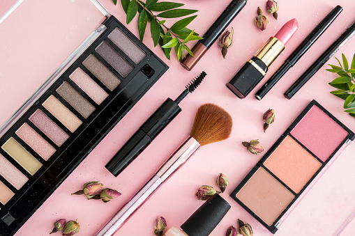 Make up natural cosmetics flat lay. Lipstick and nail polish, eye shadows and blush, brushes, pencils and rose buds against pink color background.