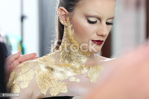 istock make up  model at mirror, gilded body paint 670434258