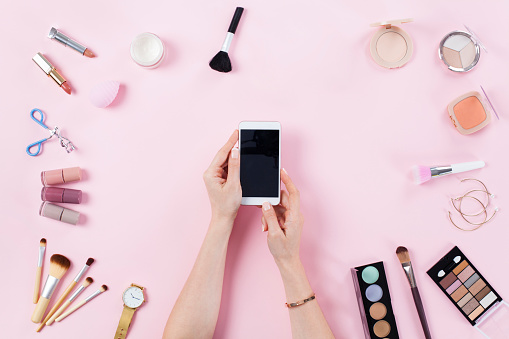 Make up products with woman holding smart phone