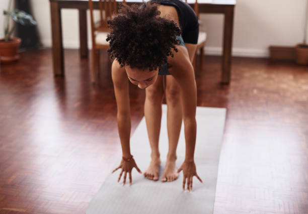 Make your home a place of good health Shot of a young woman practicing yoga at home touching toes stock pictures, royalty-free photos & images