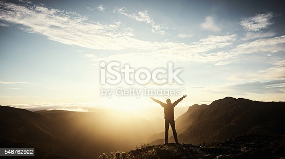 Shot of a young man embracing the morning sun while hiking in the mountains