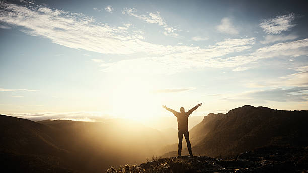 Make your own trail Shot of a young man embracing the morning sun while hiking in the mountains arms outstretched stock pictures, royalty-free photos & images