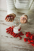 High angle view of female hands putting a bunch of red heart-shaped chocolates inside decorated jar on top of a wooden table as part of a gift for Valentine's day.