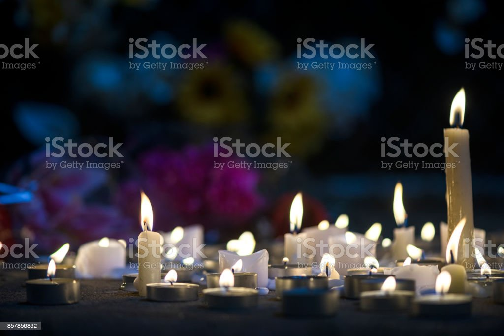 A makeshift memorial vigil with various size candles and flowers at night stock photo