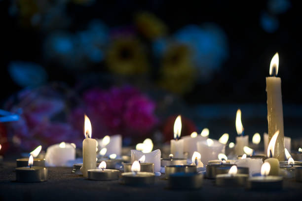 a makeshift memorial vigil with various size candles and flowers at night - candle stock pictures, royalty-free photos & images