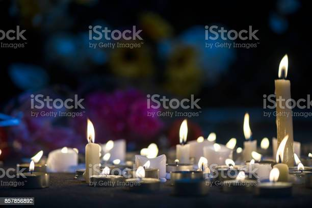A growing makeshift vigil for victims made out of various size candles on a concrete sidewalk at night with flowers and some flowers stuck in the chainlink fence in the background. These types of memorial vigils happen after a tragic event such as a mass shootings, terrorists acts or accidents.