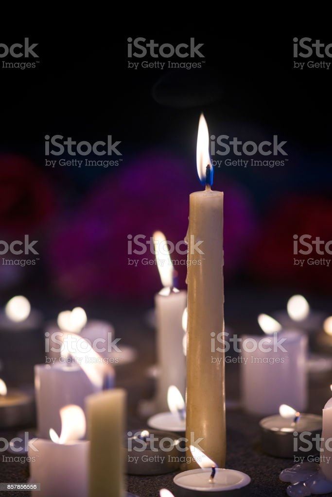 A makeshift memorial vigil with various size candles at night stock photo