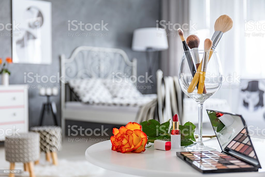 Makeup accessories lying on white round table in grey bedroom