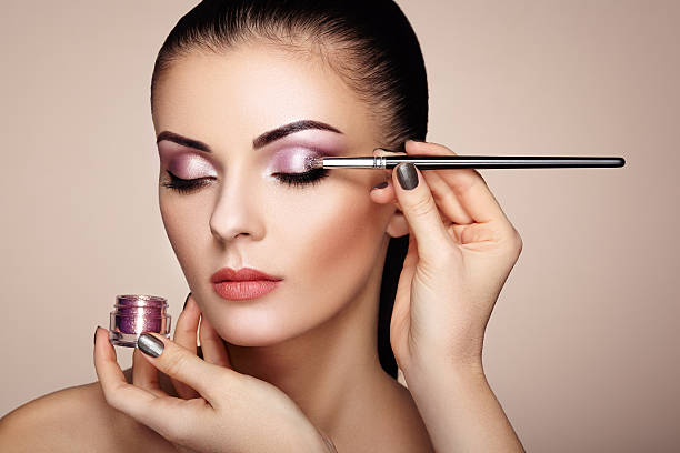 Makeup artist applies eye shadow Makeup artist applies eye shadow. Beautiful woman face. Perfect makeup. Makeup detail. Beauty girl with perfect skin. Nails and manicure stage make up stock pictures, royalty-free photos & images