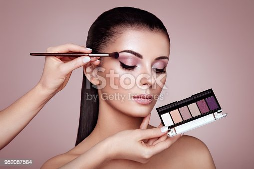 istock Makeup artist applies eye shadow 952087564