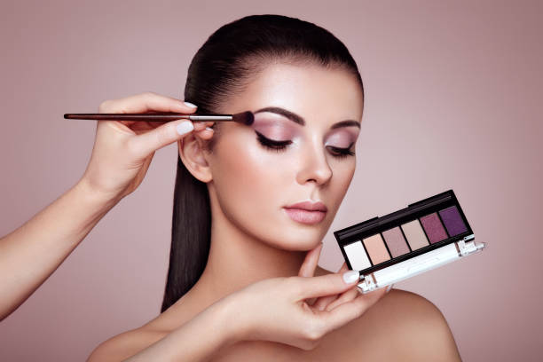 Makeup artist applies eye shadow Makeup Artist applies Eye Shadow. Beautiful Woman Face. Perfect Makeup. Make-up detail. Beauty Girl with Perfect Skin. Nails and Manicure. Eye Shadow Palette stage make up stock pictures, royalty-free photos & images