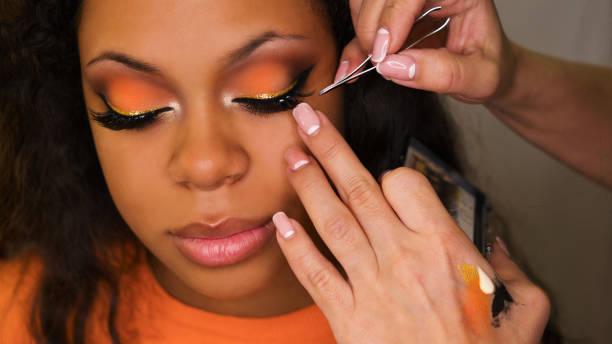 Makeup artist applies makeup on face of girl Makeup artist sticks false eyelashes of african american girl. Evening make-up. Closeup portrait. false eyelash stock pictures, royalty-free photos & images