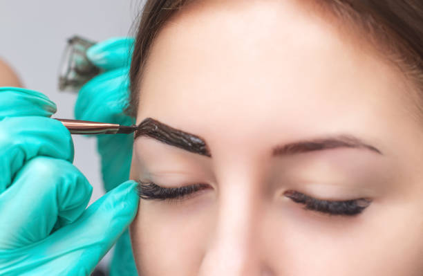 makeup artist applies paint henna on eyebrows in a beauty salon. Professional care for face. stock photo