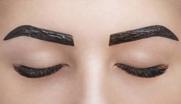 makeup artist applies paint henna on eyebrows in a beauty salon. - tattoo removal stock photos and pictures