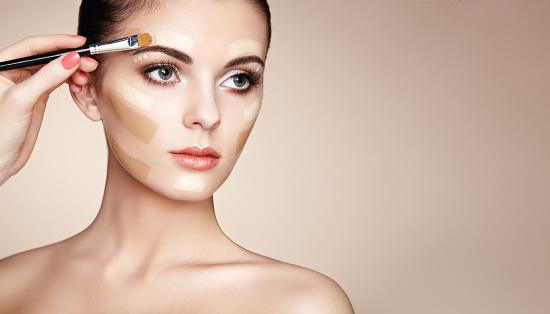 Makeup artist applies skin tone