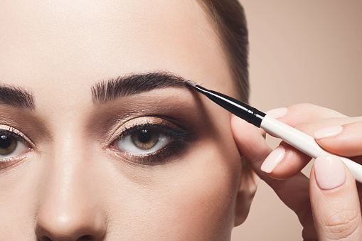 istock Make-up artist apply eyebrow shadow with brush, beauty 902969526