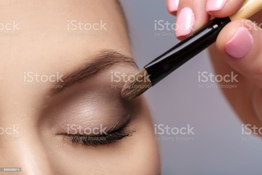 makeup artist apply makeup brush for eyes. makeup for young girl. brown eye shadow. close up - foto de stock
