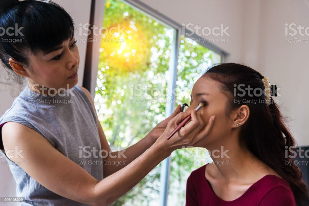 Make-up artist applying bright base color eyeshadow on model's eye and holding a shell with eyeshadow on background, close up stock photo