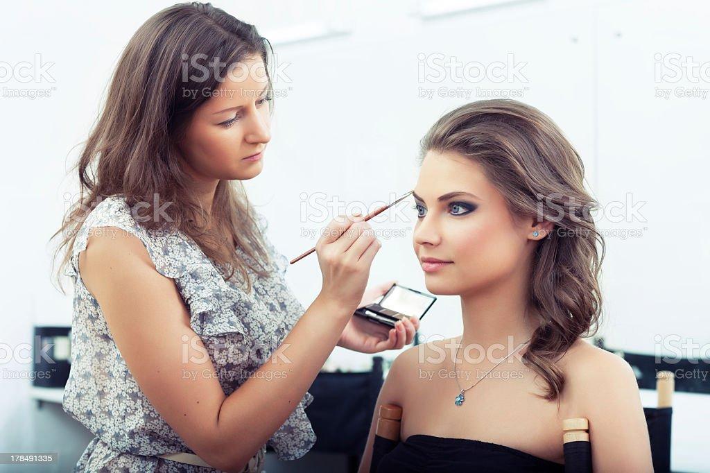 Makeup artist applying eye makeup to pretty girl stock photo