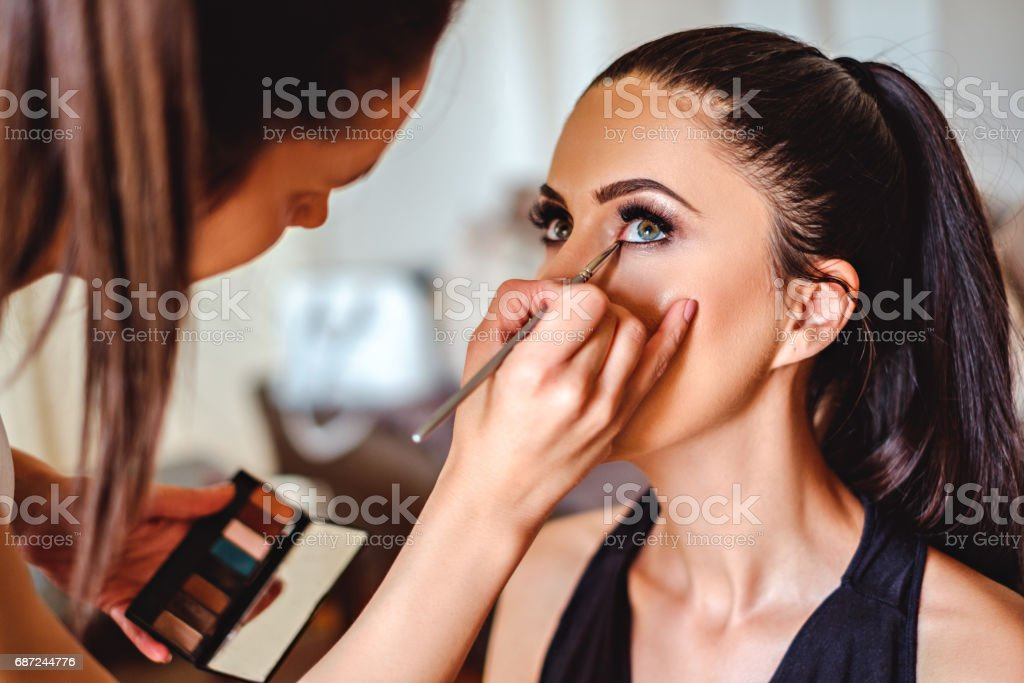 Makeup artist applying eyeshadow on a girl royalty-free stock photo
