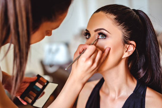 Makeup artist applying eyeshadow on a girl stock photo