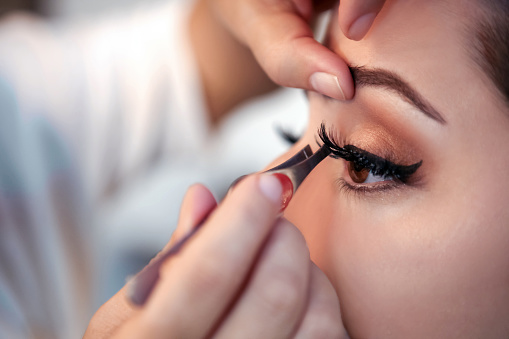 Makeup artist applying false eyelash