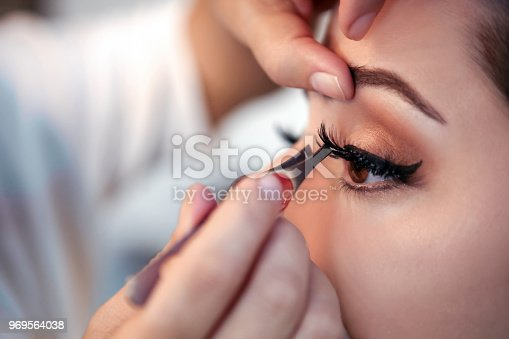 Makeup artist applying false eyelash