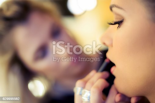 istock Makeup artist applying lipstick 629995582