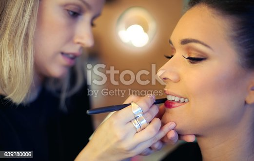 istock Makeup artist applying lipstick 639280006