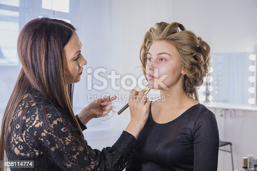 istock Makeup artist applying liquid tonal foundation on the face of 638114774