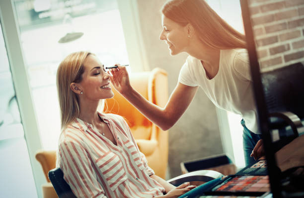 Makeup artist applying liquid tonal foundation on the face of the woman in make up room stock photo