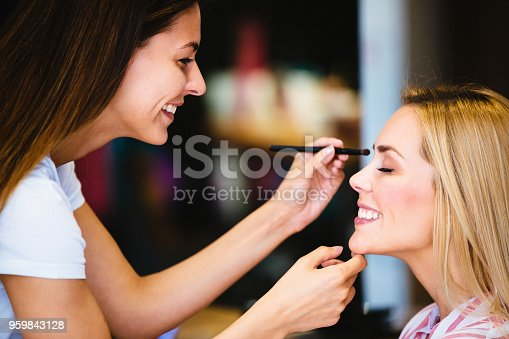 istock Makeup artist applying liquid tonal foundation on the face of the woman in make up room 959843128