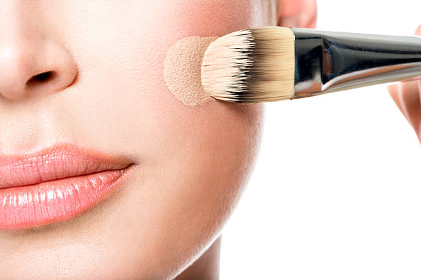 Makeup artist applying liquid tonal foundation  on the face Makeup artist applying liquid tonal foundation  on the face of the woman. Closeup photo of cheek toned image stock pictures, royalty-free photos & images