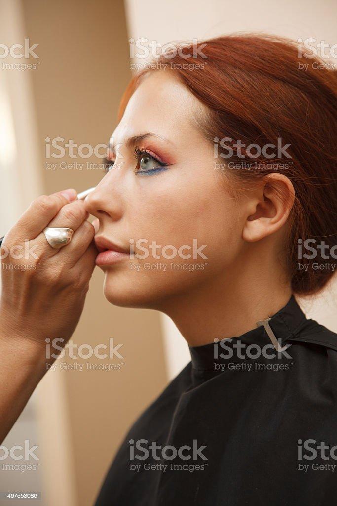 Makeup artist applying make-up on a model. stock photo