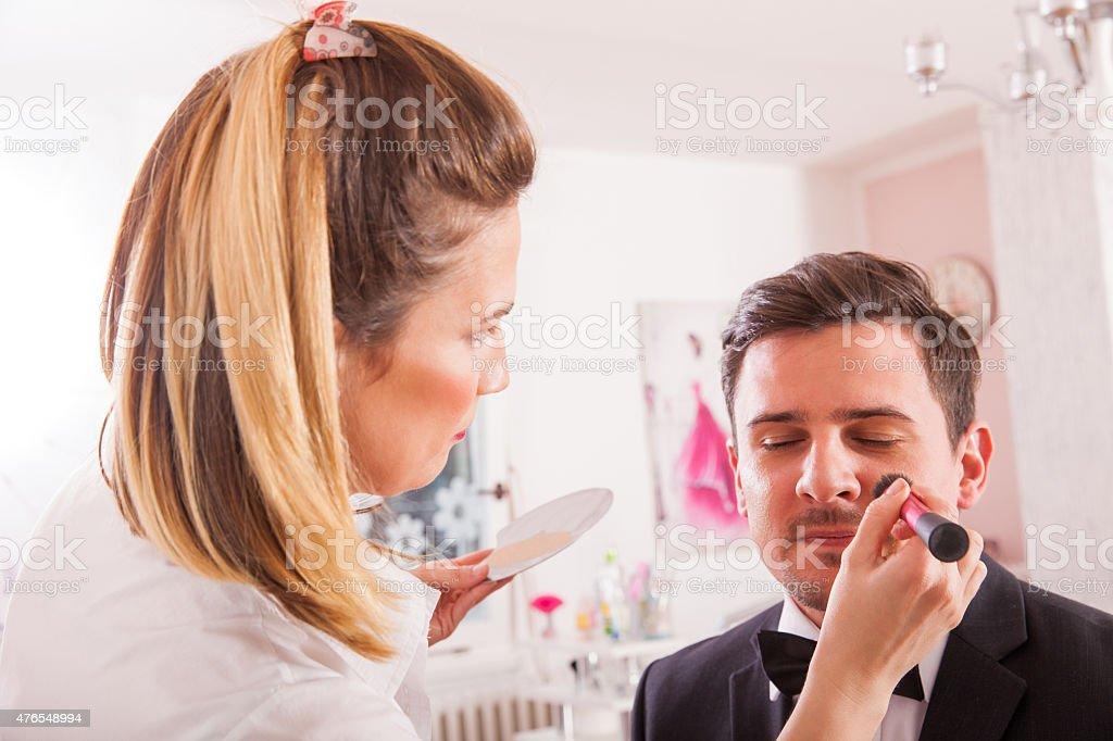 Make-up artist artist doing young man stock photo