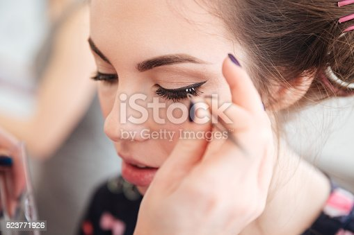 istock Makeup artist doing false lashes to young woman in curlers 523771926