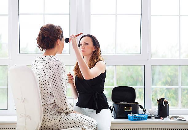 make-up-künstler macht make-up für junge schöne braut - brautstyling stock-fotos und bilder
