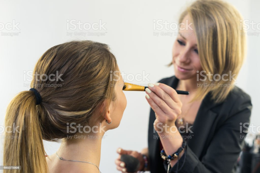 Make-up artist doing makeup to beautiful young girl foto de stock royalty-free