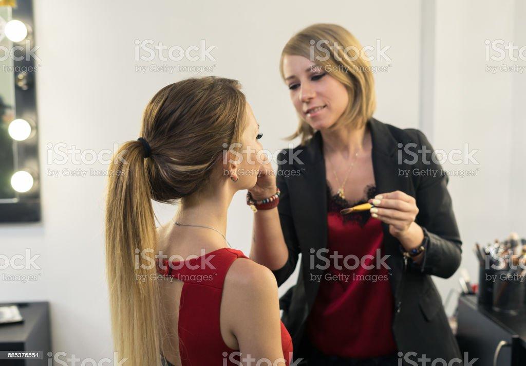 Make-up artist doing makeup to beautiful young girl foto de stock royalty-free