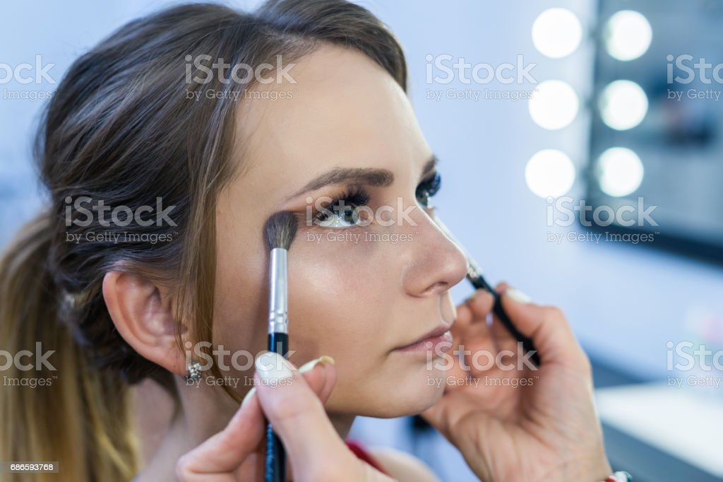 Make-up artist doing smoky eyes makeup to beautiful young girl royalty-free stock photo