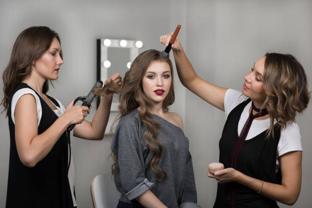 Makeup artist, hairstylist and model in beauty studio stock photo